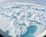 """ARCTIC OCEAN - A multi-year ice floe slides down the starboard side of the Coast Guard Cutter Healy Aug. 12, 2009, as the ship heads north into even thicker ice. """"You can tell that this is a multi-year ice floe by the light blue melt ponds that have formed on top of the floe,"""" said Pablo Clemente-Colón, chief scientist at the U.S. National Ice Center."""